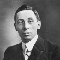 Image: A photographic head-and-shoulders portrait of a young man wearing a suit and wire-rimmed spectacles