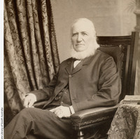 Image: man with beard sitting in chair