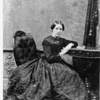 Image: woman in long dress sitting on a chair and leaning on a table.