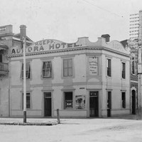 Image: A white, two-storey building stands at the corner of two dirt streets. The words 'Aurora Hotel' are painted on the side of the building