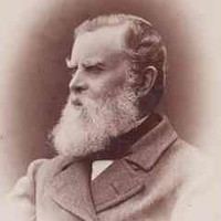 Image: A photographic head-and-shoulders portrait of a middle-aged bearded man wearing a cravat and overcoat