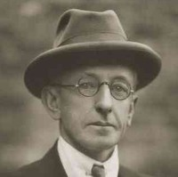 Image: A photographic head-and-shoulders portrait of a clean-shaven middle-aged man. The poet looks directly at the camera through round, wire-rimmed spectacles. He is wearing a collar, tie and jacket and a fedora hat
