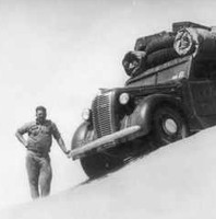 Image: Man stands leaning on heavily loaded truck perched on top of a sandhill