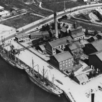 Image: An aerial photograph of a complex of large, multi-storey brick buildings and corrugated metal structures located next to a river. Two sailing ships are moored alongside a wharf associated with the complex