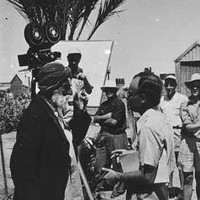 Image: A group of Caucasian men with film equipment observe a conversation between two other men, one of whom is elderly and dressed in Afghan attire