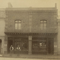 Image: Two men in Victorian attire stand in front of a two-storey brick and bluestone building