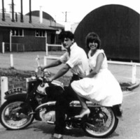 Image: Man and woman on motorbike with curved tin buildings behind