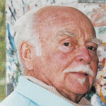 Image: Elderly man with mustache poses in three quarter profile in front of artwork