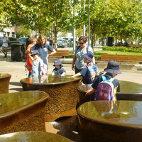 Image: children playing with the water in a fountain
