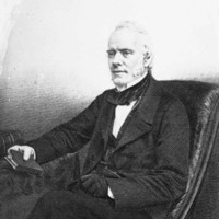 Image: A lithograph of a middle-aged man in Victorian attire seated at a table and holding a book