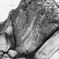 Black and white photo of large rock with words scratched deep on in its face