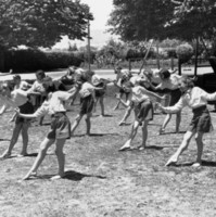Image: A group of girls perform exercises in a grassy ground surrounded by trees and playground equipment