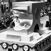 Image: parade of floats watched by crowds lining street