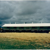 Image: large curved tin building being towed on the back of a truck