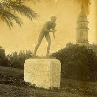 Image: sepia toned photo of statue of naked boy in running pose in a park
