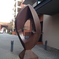 Image: steel quadrangle-shaped sculpture with rounded edges and a geometric hole in the middle