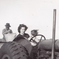 A woman and a small child sitting behind the steering wheel of a tractor.  A man behind them is sewing up a hessian bag.