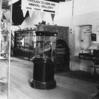 Black and white image of old museum display showing large wooden plinth with staircase on top.