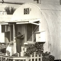 Image: woman at door of curved tin building