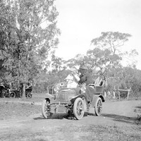 Image: old open top car on dirt road
