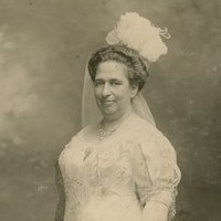 Image: black and white photo of woman standing in white dress and veil