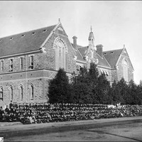 Image: Hundreds of schools students in black uniforms pose in lines outside a large symmetrical stone building with decorative brickwork between floors, two huge arched windows on the front gable ends and smaller windows on the sides.