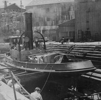 Image: A tugboat sits on stands in a dry-dock. A group of men sit facing the vessel in the foreground