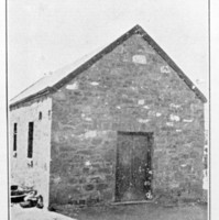 Image: black and white image of stone building with peaked roof.