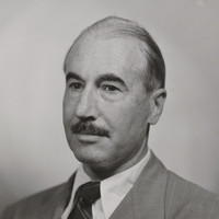 Image: A formal photographic head-and-shoulders portrait of a balding, moustachioed middle-aged man in a suit and tie