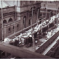 Image: A group of men lay bricks on the roof of a large building.