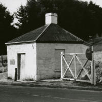 Image: Toll house and gate next to modern road