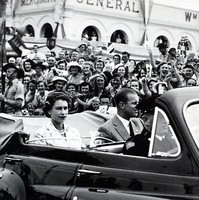 Image: Black and white photo of people in car surrounded by a crowd