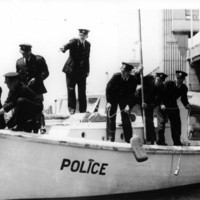 Image: A group of policemen stand on a small motor boat. One of the policemen is pointing and directing others to perform specific activities