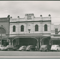 Image: 1950s era cars are parked on the street outside a two-storey terraced building with arched windows, a balcony and a stepped parapet with a sign reading Empire Theatre