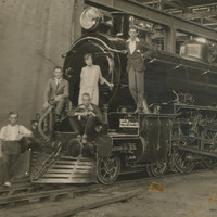 Image: The front of a train sitting in a large shed with five people sitting on the frond looking towards the camera
