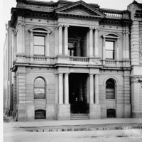 Image: two men in suits pose on the front steps of a two-storey stone building with recessed main entrance flanked by stone columns which are repeated on the floor above framing a balcony and topped with a simple triangular pediment.