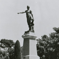 Image: A statue of a man upon a plinth surrounded by formal gardens. His arm is outstretched with his finger pointing.