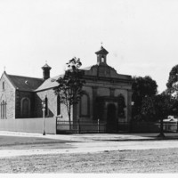 Image: a small stucco church with a belfry and small arched porch. Most of the windows have been filled in.