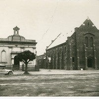 Image: Two Church buildings, old and new are side by side. The smaller old building is topped by a belfry. In front of it is a small tree. A tourer car is parked by the kerb. The larger building is made of dark stone, has a plain facade and butresses.