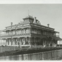 Image: large two story building with smaller third story and wrap around verandah