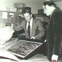 Image: Black and white photograph of two men in suits. They are standing around a just unwrapped painting of a ship