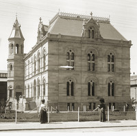 Image: Two women in early 20th century clothing, one with a sun umbrella, stroll past a large stone building with two main floors as well as basement and attic space.