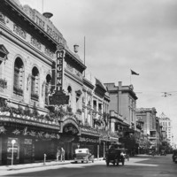 Image: a very ornate theatre building with plants hanging from and on top of its verandah as well as in window boxes on the second storey.