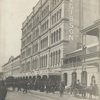 Image: a large number of people in early 20th century clothing gather outside a five storey building with a decorative iron verandah