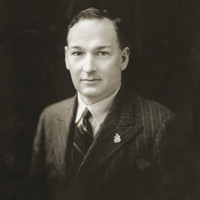Image: Black and white portrait photograph of the upper body of a man dressed in formal attire