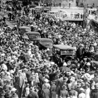 Image: Four 1940s-era auto-mobiles move through a crowd of people gathered for a ceremony