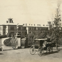 Image: a horse drawn carriage is pulled up alongside large gates. Beyond the gates a long drive curves around to meet a large two storey stone building with arched windows and a large number of chimneys.