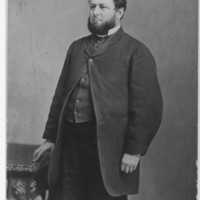 Image: A photographic portrait of a bearded man standing next to a table. The man is wearing an overcoat and other mid-nineteenth century clothing