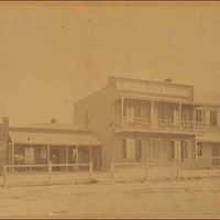 Image: a row of three terraced buildings. The one on the left is one storey with a verandah under which people stand. In the centre is a two storey building with a balcony and a parapet sign. To the right is another two storey building with a verandah.