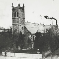 Image: A large stone church building with a tower topped by four spires stands at the corner of two dirt roads. A man stands in front of the churchyard fence